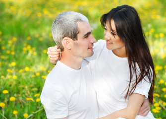 Young loving couple at the green grass with dandelion