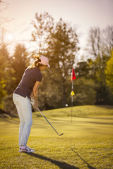 Female golf player pitching towards flag.