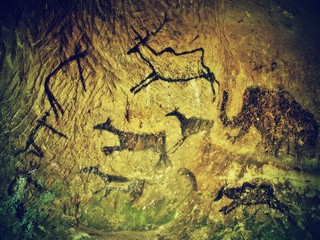 Abstract art in sandstone cave. Black carbon paint of hunting