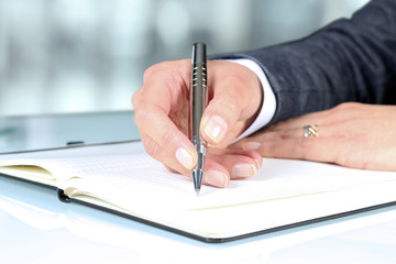 Woman's hand using a pen noting on notepad