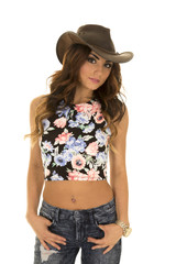 woman in floral shirt cowgirl hands in pockets