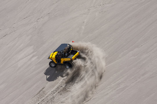 Yellow side by side buggy racing by in the sand dunes