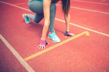 athlete on starting blocks at stadium track preparing for sprint