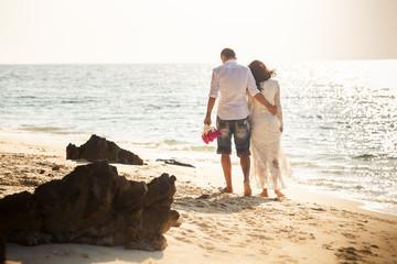 bride and groom walk along sea