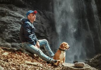 Man with dog sitting near waterfall