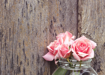 Bunch of pink roses against an old wooden wall background