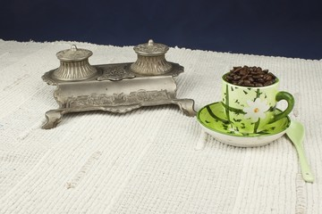 cup of coffee beans on the table with Art Nouveau inkwell