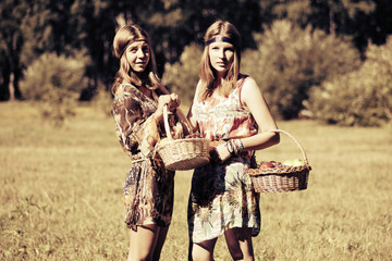 Happy young fashion girls with a fruit basket walking on nature