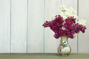 lilacs in a vase on a wooden background