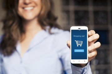 Shopping cart on the screen. Woman holding her mobile phone.