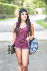 Beautiful girl walking at park holding a skateboard.