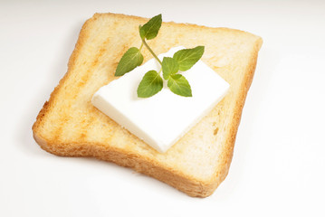 A crusty toasted bread with cheese and a basil leave isolated
