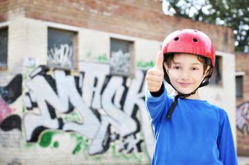 Bambino con casco da skateboard fa ok con mano