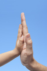 Father and son in high five gesture on sky background
