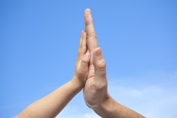 Father and son in high five gesture on a sky  background