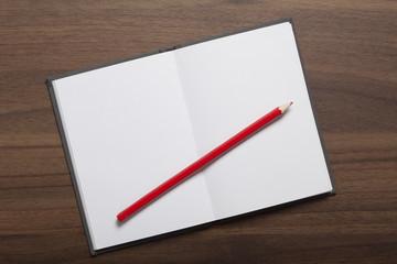 Leeres Blatt in Notizbuch mit rotem Stift auf Holz