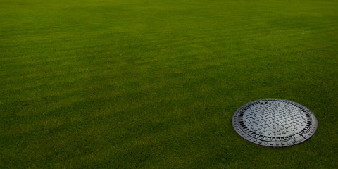 Sewer hatch on the green meadow.