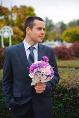 Groom with wedding bouquet in his hands