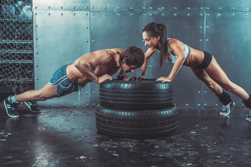 Wall Mural - Sportswomen. Fit sporty woman and man doing push ups on tire