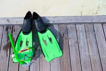 Mask, snorkel and fins for snorkeling on wooden jetty