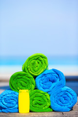 Close up of colorful towels and sunscreen bottle background the