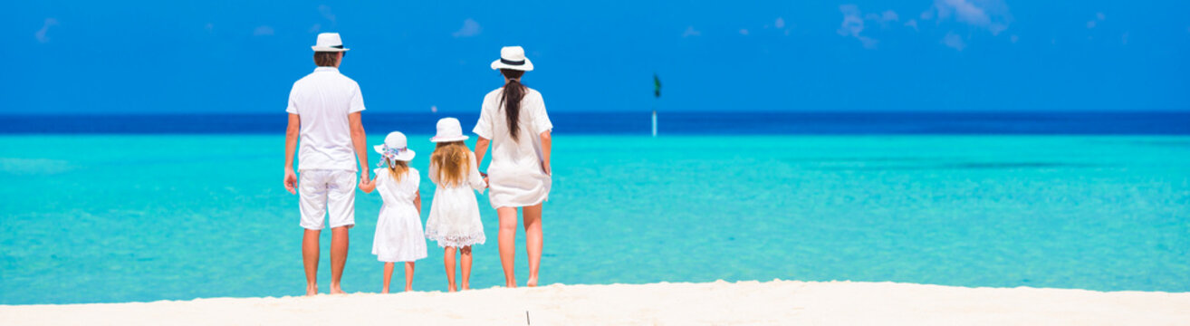 Beautiful tropical beach landscape with family in white enjoying
