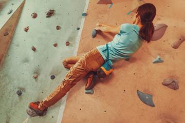 Climber young woman exercising indoor