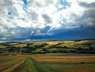 Blick auf eine Landschaft mit Feldern und dunklen Wolken