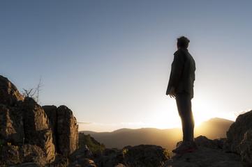 Mujer en lo alto de la montaña contempla el atardecer/Horizontal