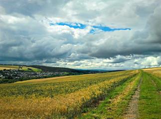 Feldweg in einer Landschaft mit Feldern und Wolken am Himmel