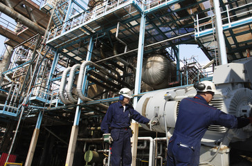 oil and gas workers with pipelines machinery inside refinery
