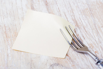 Blank picture frame paper with fork on a wooden table