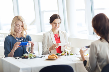 women with smartphones taking picture of food