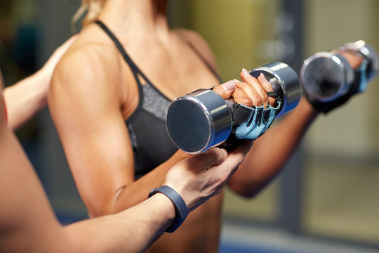 woman with dumbbells flexing muscles in gym