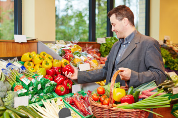 Man buying red pepper in supermarket