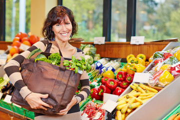 Smiling woman with bag full of vegetables