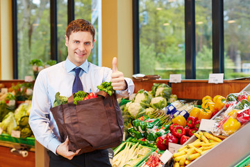 Man with shopping bag holding thumbs up