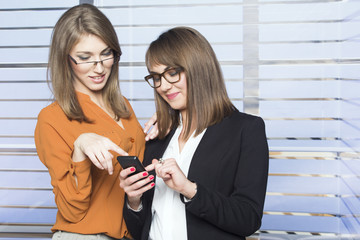 Two businesswomen looking at pictures on phone