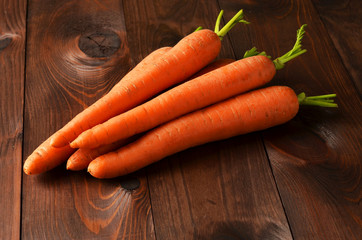 Fresh carrots on brown wooden background
