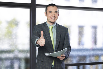 Businessman holding documents and giving thumbs up