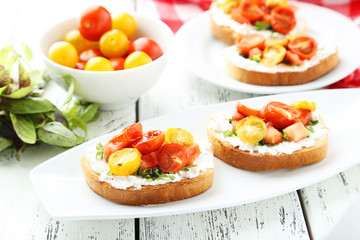 Tasty fresh bruschetta with tomatoes on plate on white wooden ba