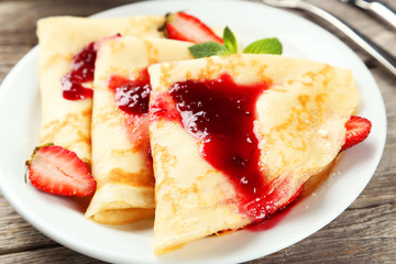 Pancakes with strawberry on plate on grey wooden backgound