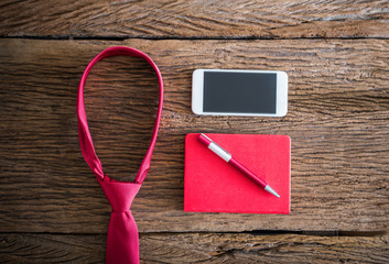 red necktie, pen, note book, smartphone on wooden table
