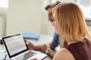 zwei kollegen im büro planen zusammen etwas am laptop