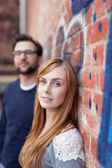modernes junges paar lehnt draußen an einer backstein-wand