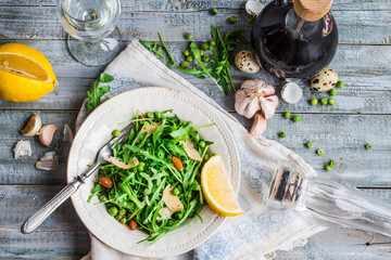 fresh green salad with arugula, cheese, almonds, lemon and olive