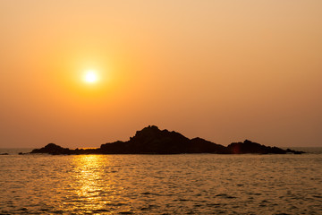 Rocky island silhouette and sunset