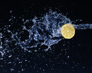 Half a lime falling into the water isolated on a black