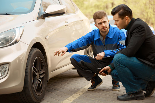 Mechanic and Customer Discussing Problem With Car.