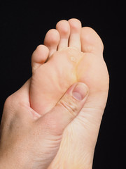 Pressure point massage under foot with thumb isolated towards bl